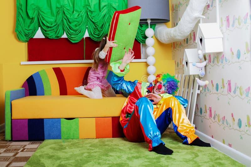 愉快的小女孩打有一个大枕头的小丑 免版税库存照片