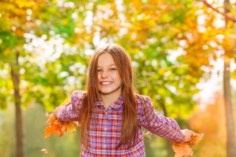 愉快的小女孩投掷槭树在天空中离开 免版税库存照片