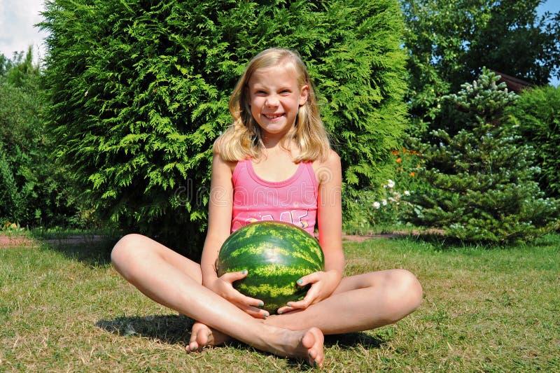 愉快的小女孩用一个大西瓜 免版税库存照片