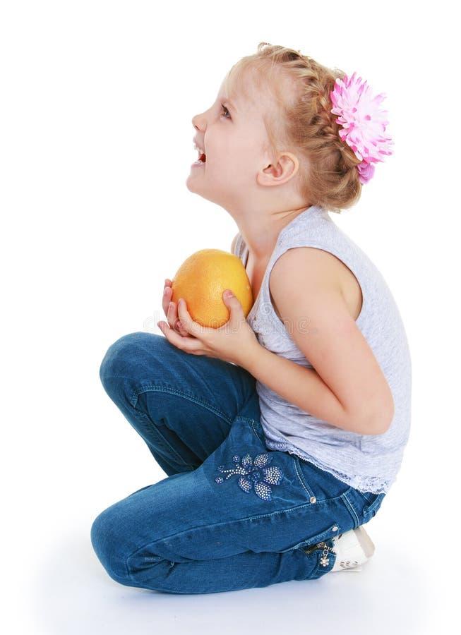 愉快的小女孩用一个桔子在她的手上 图库摄影