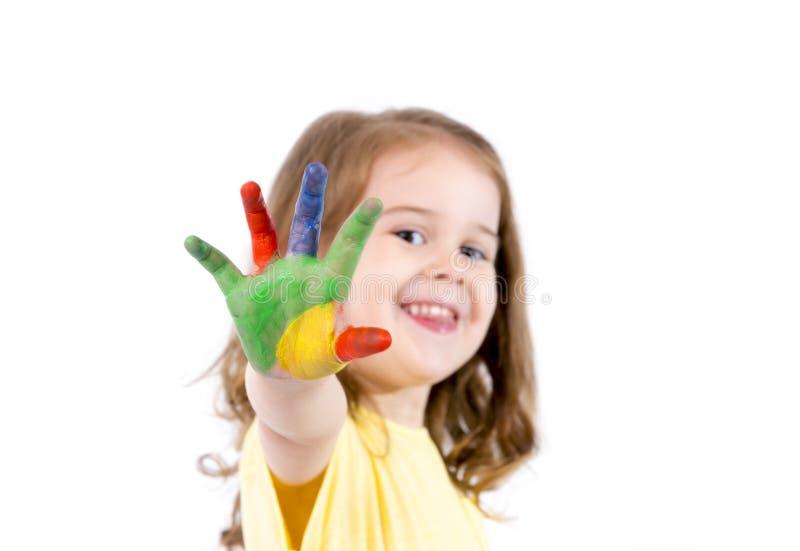愉快的小女孩用在颜色绘的手 免版税库存照片