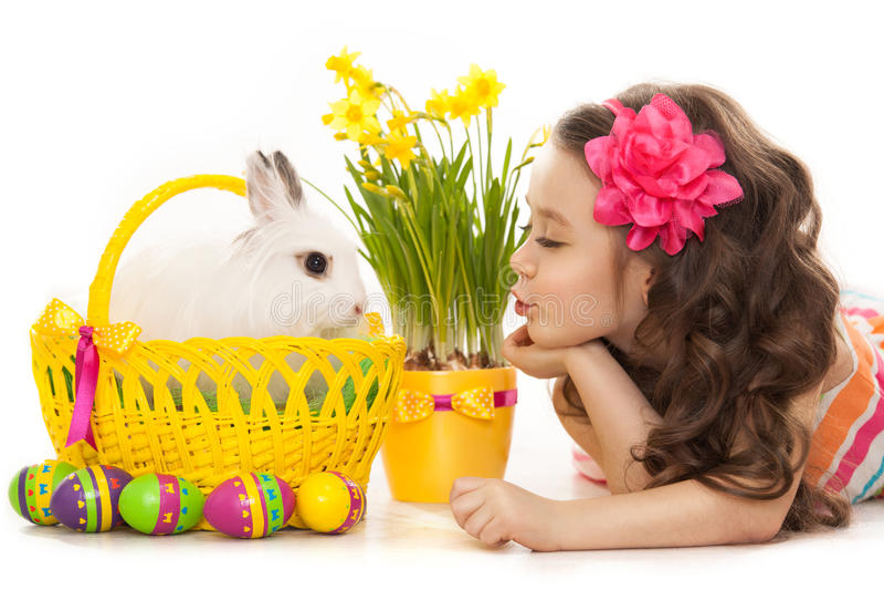 愉快的小女孩用复活节兔子和鸡蛋 免版税图库摄影