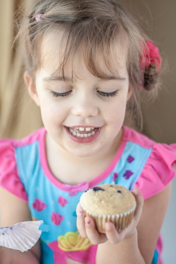 愉快的小女孩用松饼 库存照片