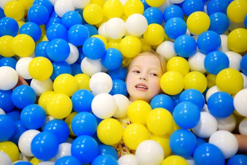愉快的小女孩获得乐趣在球坑在孩子室内戏剧中心 使用与在操场球水池的五颜六色的球的孩子 图库摄影