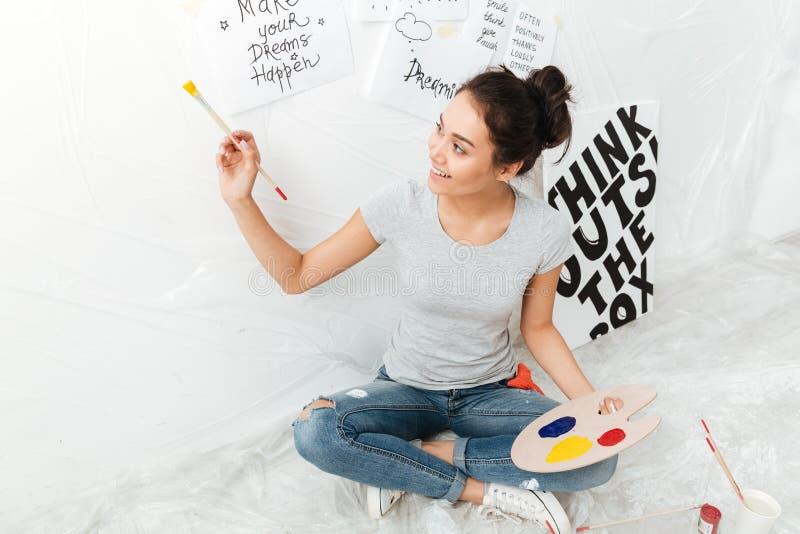 愉快的小姐艺术家坐在白色背景的地板 库存图片