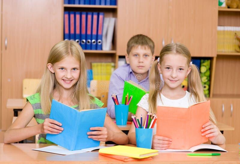 愉快的小学生画象有书的 免版税库存图片