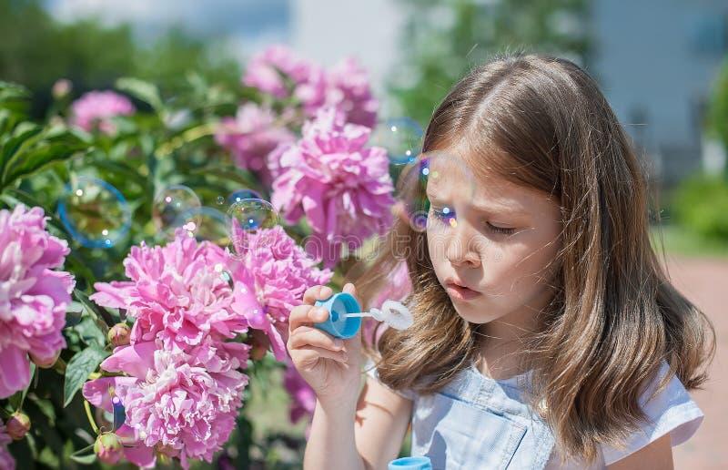 愉快的小孩吹的肥皂泡户外在夏天公园 开花的桃红色牡丹芍药属,牡丹花 r 免版税库存图片
