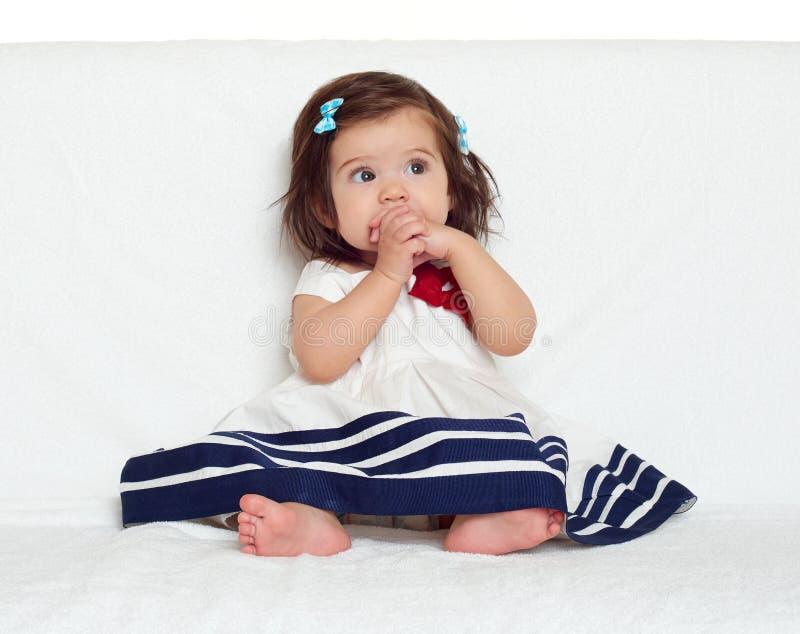 愉快的小孩女孩坐白色毛巾、愉快的情感和面孔表示,非常惊奇,在嘴的手指 库存照片