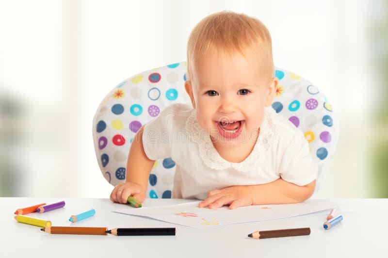 愉快的小孩子画与色的铅笔蜡笔 免版税库存照片