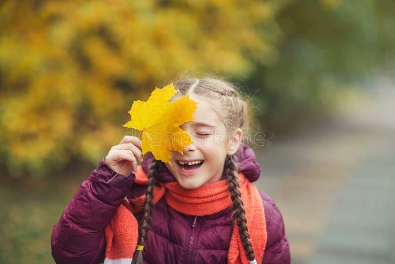 愉快的小孩,女婴在秋天的笑和演奏叶子在自然步行户外 免版税库存图片