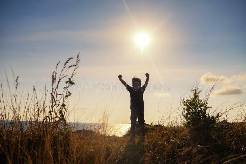 愉快的小男孩伸手可及的距离山山顶 库存照片