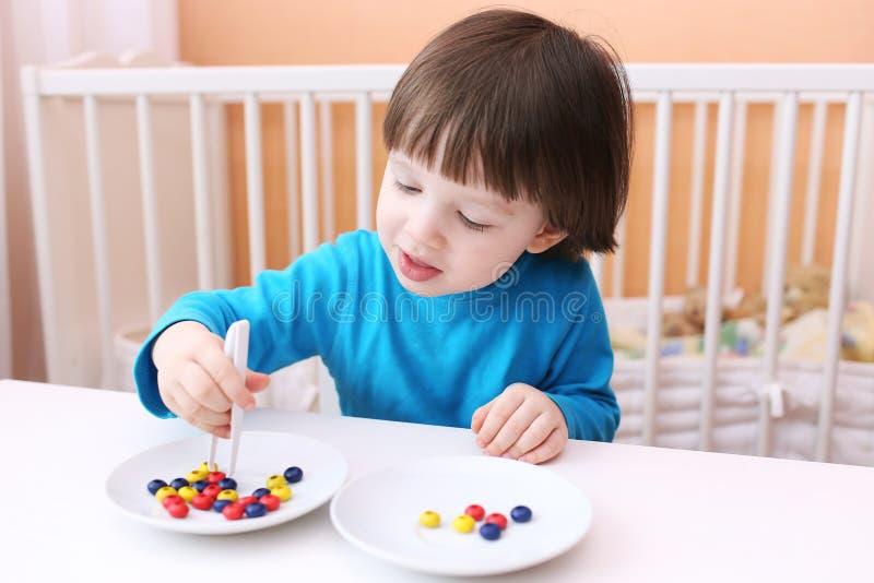 愉快的小男孩使用与夹子和小珠 教育playi 免版税库存图片