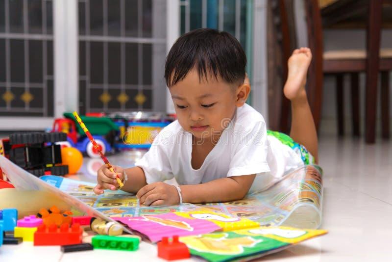 愉快的小男孩图画和读书 免版税库存照片