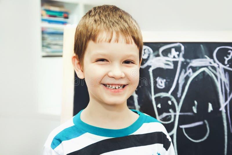 愉快的小男孩在与字母表的校务委员会面前 educ 免版税图库摄影