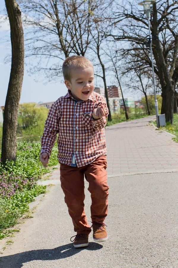 愉快的小男孩在他的手上拿着一只蚂蚁 库存照片