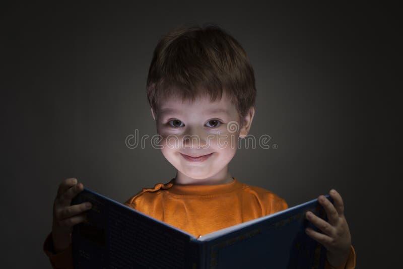愉快的小男孩在黑背景读了书 免版税库存照片
