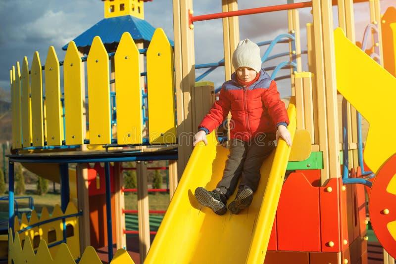 愉快的小男孩有乐趣和滑在五颜六色的现代操场在公园 免版税图库摄影