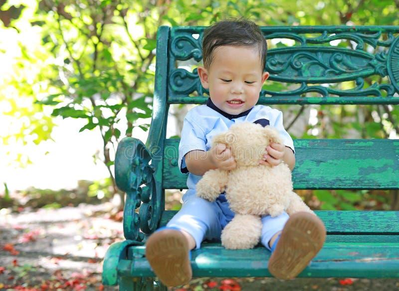 愉快的小男孩画象有玩具熊的在庭院里 免版税库存图片