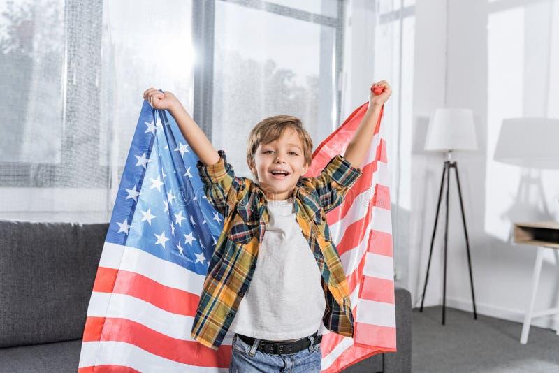 愉快的小男孩画象有美国国旗的在看照相机的手上 免版税库存图片