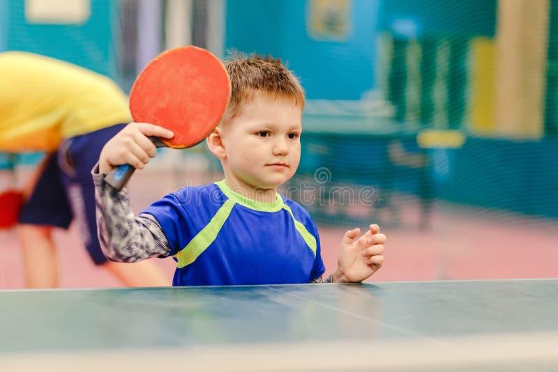 愉快的小男孩站立在网球大厅里的,网球大厅,网球拍,乒乓球 免版税库存照片