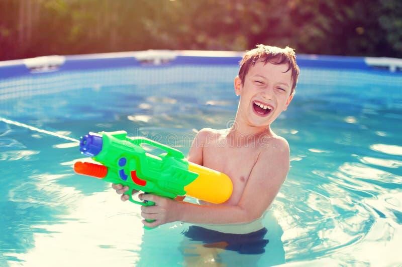 愉快的小男孩笑和射击与喷枪 库存照片