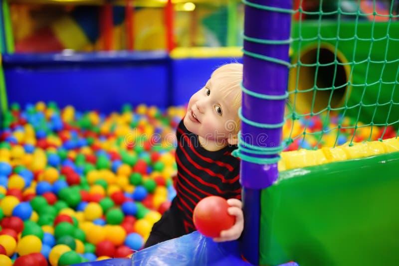 愉快的小男孩获得乐趣在与五颜六色的球的球坑 免版税库存照片