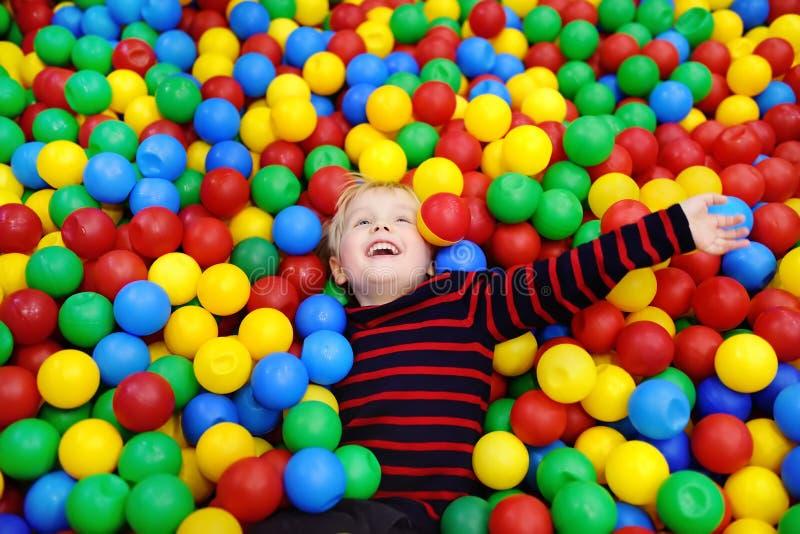 愉快的小男孩获得乐趣在与五颜六色的球的球坑 库存照片
