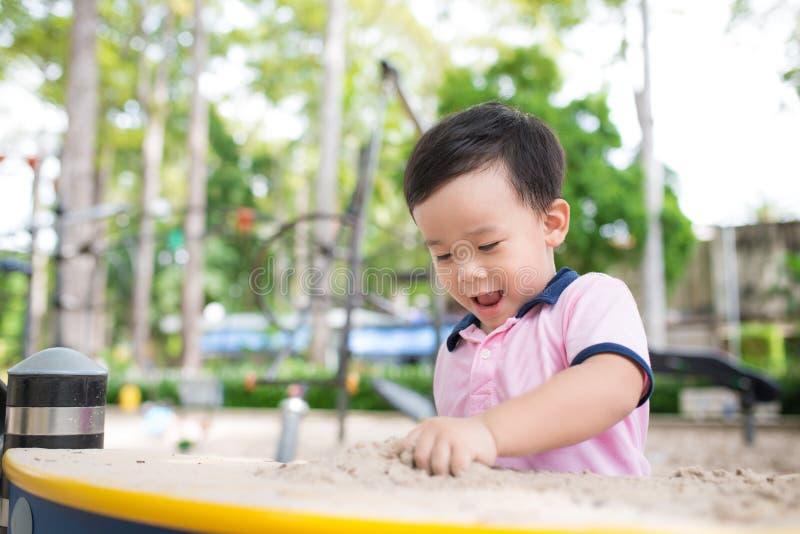 愉快的小男孩获得乐趣在操场在夏天 库存图片