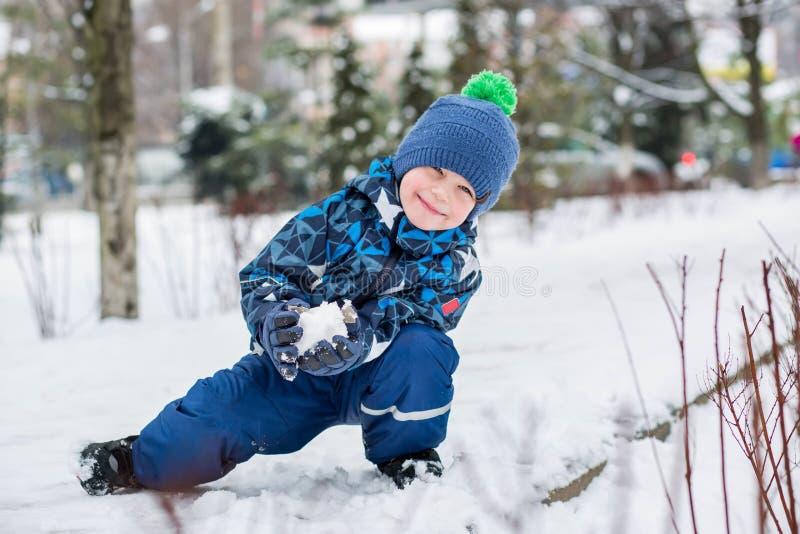 愉快的小男孩雕刻雪球 免版税库存图片