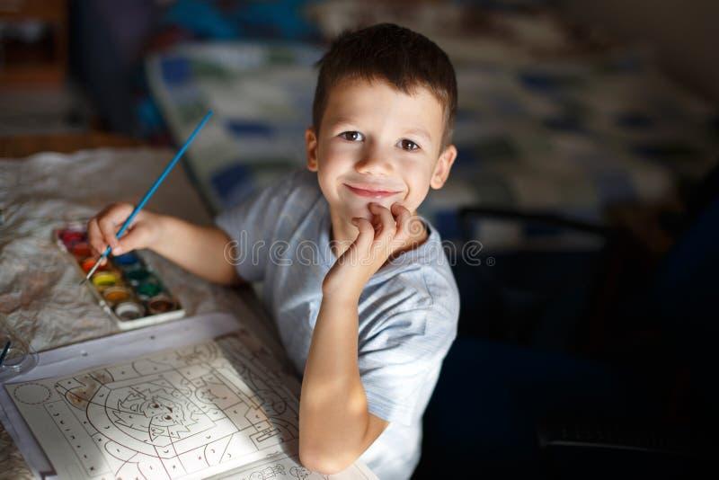愉快的小的学龄前儿童男孩绘画彩图 库存照片