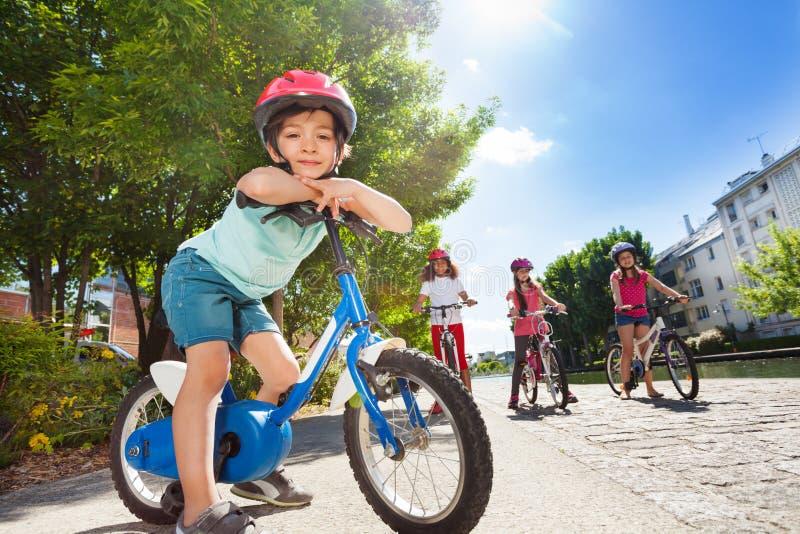 愉快的小的骑自行车者骑马自行车在夏天城市 库存照片