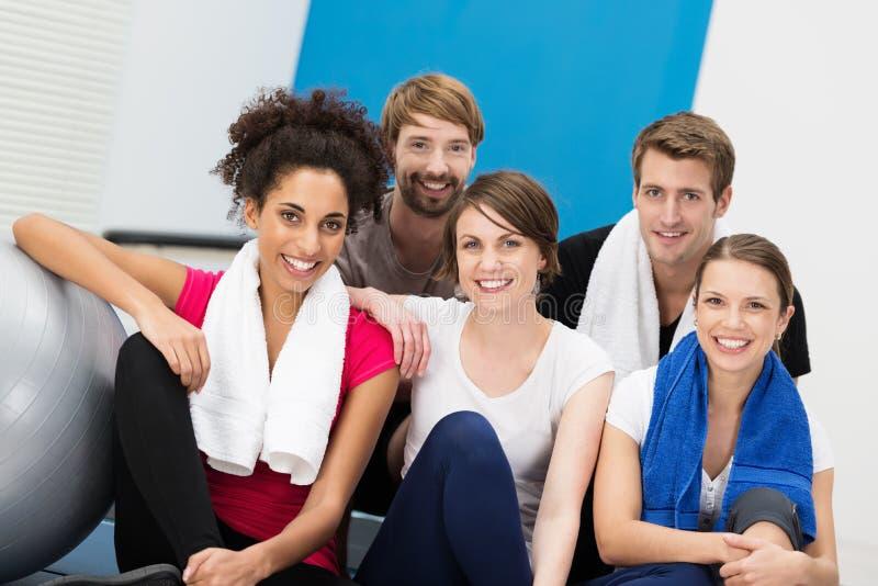 愉快的小组健身房的年轻朋友 免版税库存图片