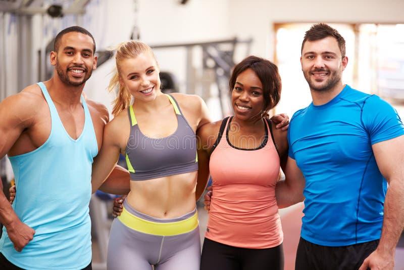 愉快的小组有胳膊的健身房伙计在彼此附近 免版税库存图片