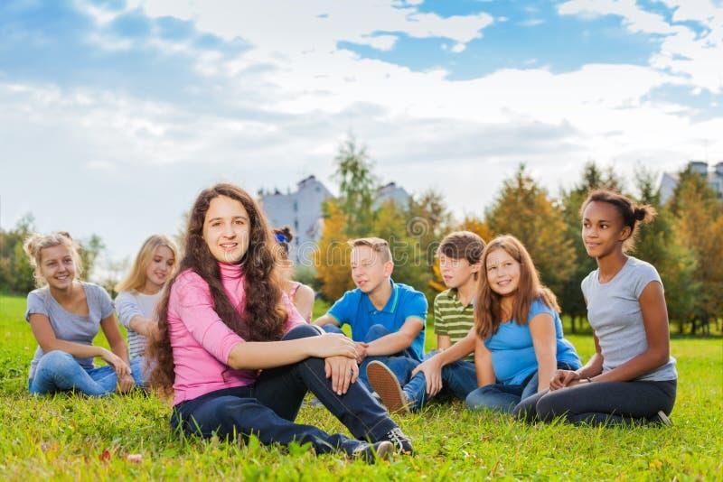 愉快的小组朋友一起坐草甸 免版税库存照片