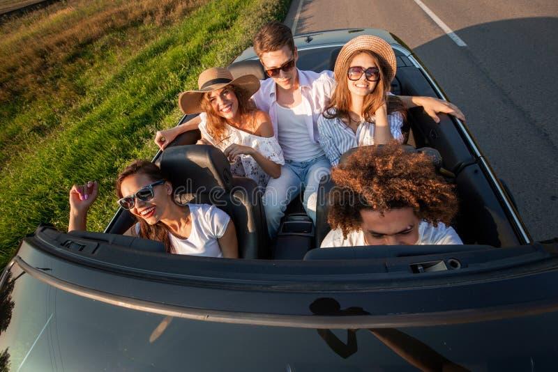 愉快的少女公司和人在一条黑敞篷车汽车路坐一好日子 顶视图 库存图片