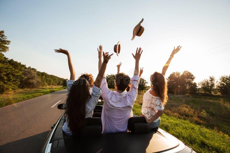 愉快的少女公司和人在一条黑敞篷车汽车路坐和投掷他们的帽子在日落 免版税库存图片
