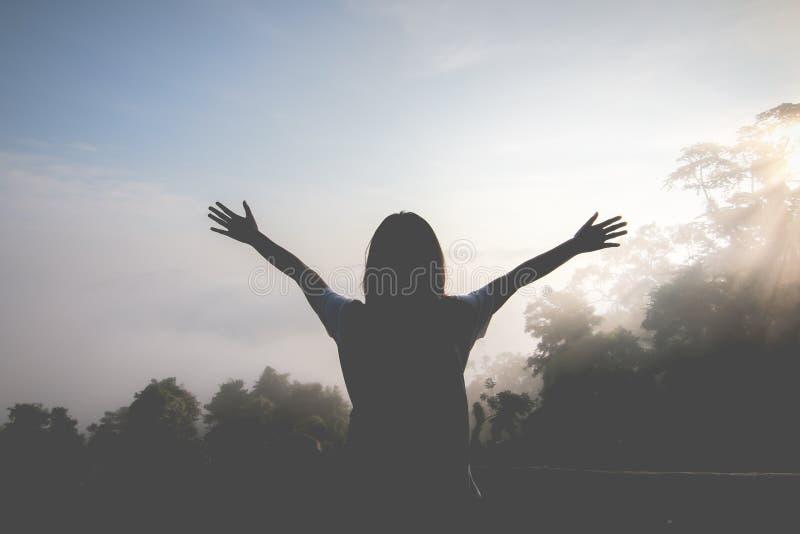 愉快的少女喜欢挑运 观看早晨太阳的黎明在山的 感觉刷新并且加强您的生活 库存图片