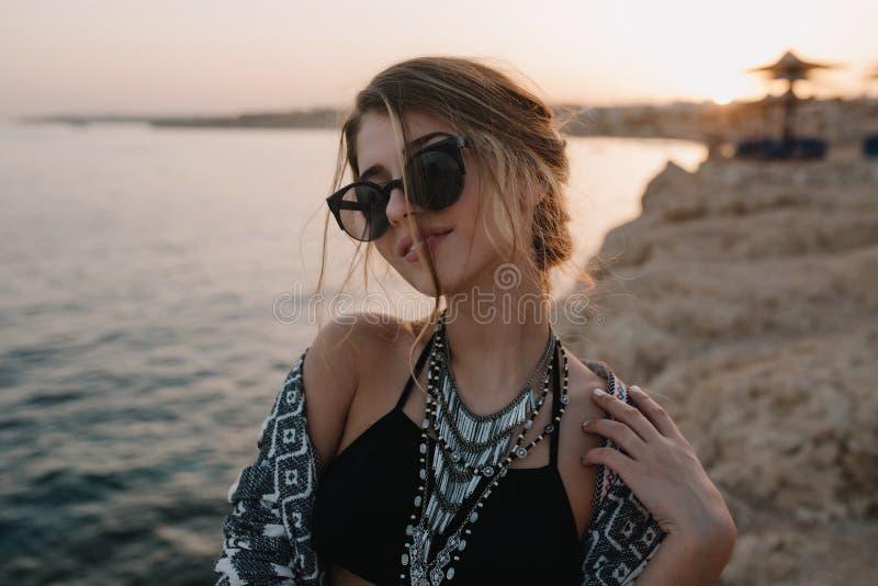 愉快的少女在度假,在海滩的射击 佩带的黑泳装,太阳镜,时髦的项链,羊毛衫 库存照片