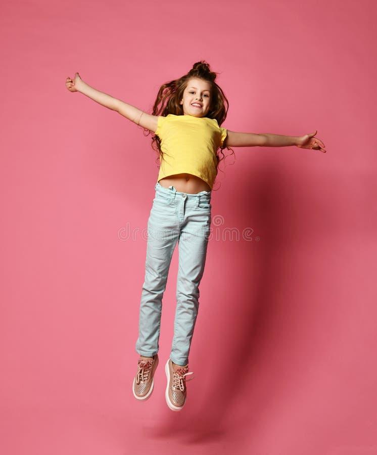 愉快的少女或青少年的女孩的牛仔裤和高黄色T恤杉的跃迁的,如她在天空飞行高与她的胳膊传播 免版税库存图片