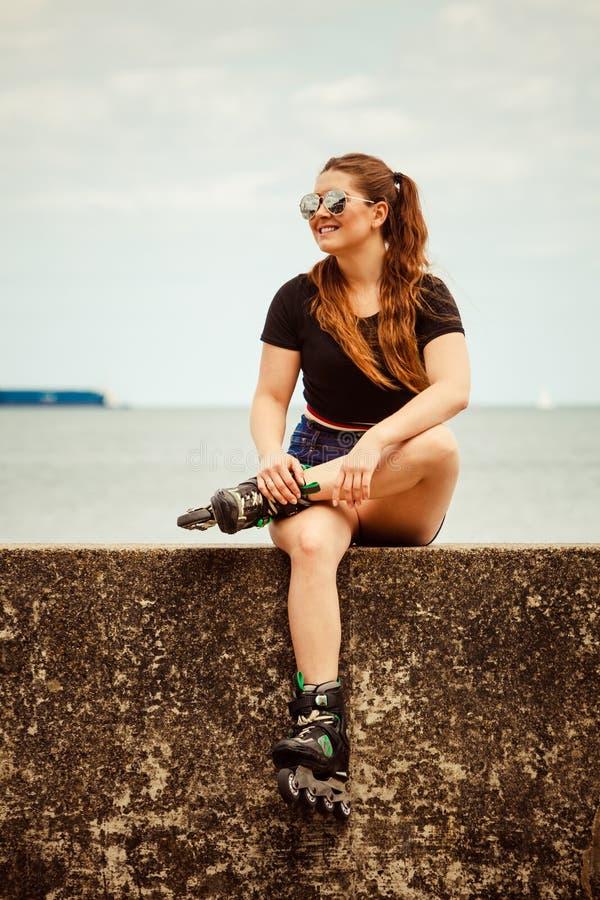 愉快的少妇佩带的溜冰鞋 免版税库存照片