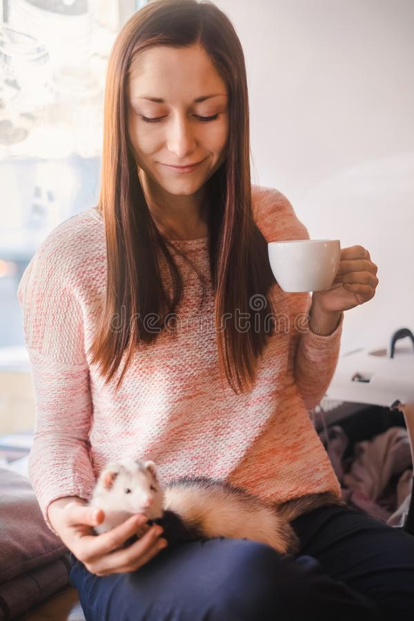 愉快的少妇和她的宠物白鼬在咖啡馆 免版税库存图片
