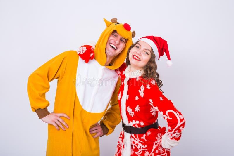 愉快的少妇在圣诞老人帽子和人鹿狂欢节服装的  乐趣、假日、笑话和圣诞节概念 免版税库存照片