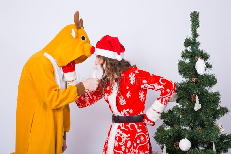 愉快的少妇在圣诞老人帽子和人鹿狂欢节服装的  乐趣、假日、笑话和圣诞节概念 库存照片