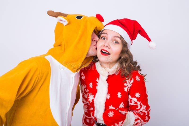 愉快的少妇在圣诞老人帽子和人鹿狂欢节服装的  乐趣、假日、笑话和圣诞节概念 免版税库存图片