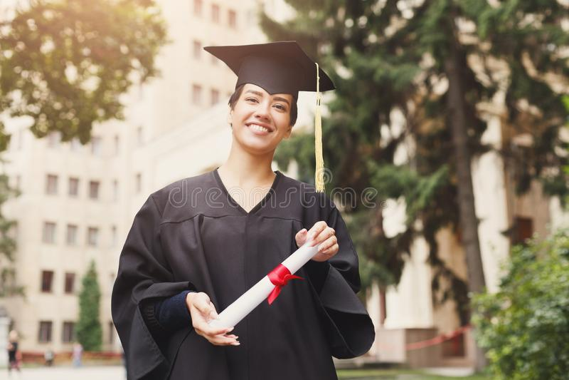 愉快的少妇在她的毕业典礼举行日 免版税图库摄影