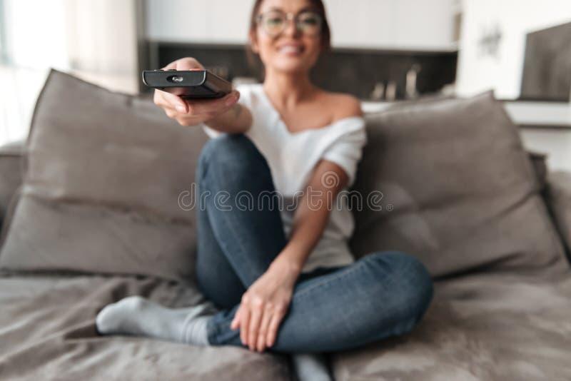 愉快的少妇在家坐沙发手表电视 库存图片