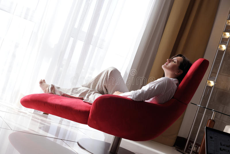 愉快的少妇在沙发在家放松 免版税库存图片