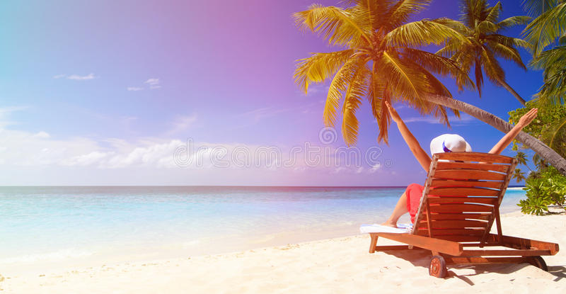 愉快的少妇坐椅子在海滩 库存图片