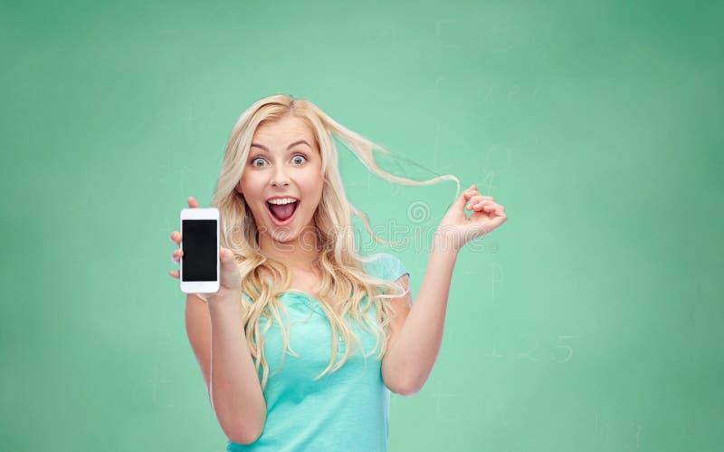 愉快的少妇或十几岁的女孩有智能手机的 免版税库存照片