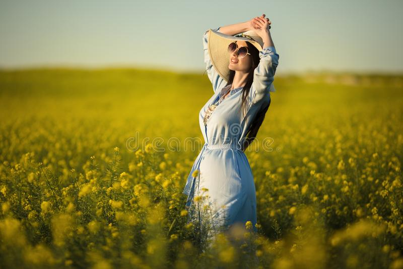 愉快的少妇戴有野花花束的时尚帽子在黄色领域的在日落光 免版税图库摄影